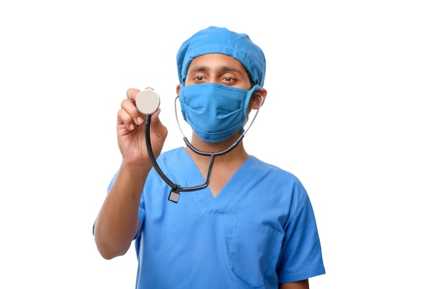 Junger indischer männlicher doktor, der in der hand stethoskop auf weißem hintergrund hält.