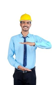 Junger indischer männlicher ingenieur, der gelbe farbe schutzhelm auf weißem hintergrund trägt.