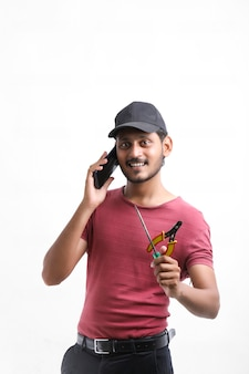 Junger indischer männlicher techniker oder ingenieur repariert elektronische geräte