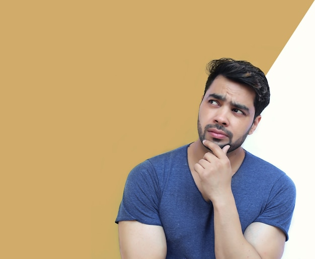 Junger indischer mann denkt an gedankenblase auf weißem hintergrund