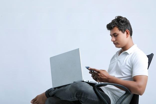 Junger indischer mann, der am laptop arbeitet und smartphone verwendet.
