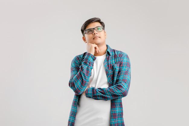 Junger indischer mann, der auf weiß denkt