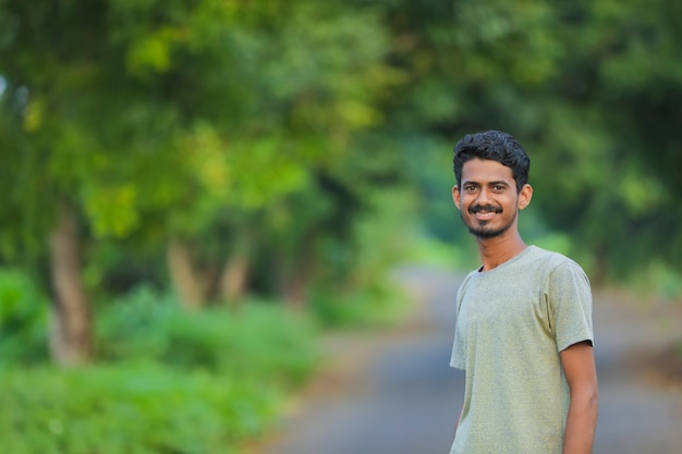 Junger indischer mann, der ausdruck über naturhintergrund zeigt