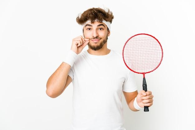 Junger indischer mann, der badminton mit den fingern auf den lippen spielt, die ein geheimnis halten.
