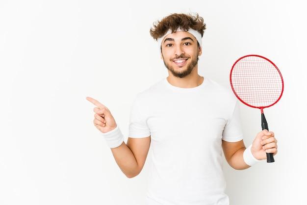 Junger indischer mann, der badminton spielend lächelt und beiseite zeigt und etwas an der leeren stelle zeigt.