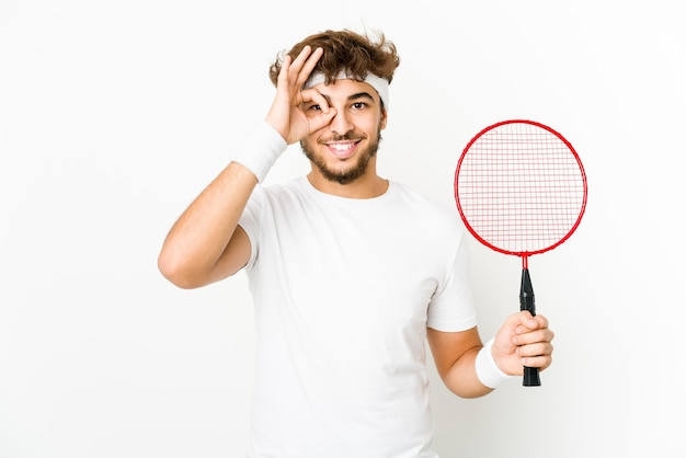 Junger indischer mann, der badminton spielt aufgeregt aufgeregt hält ok geste auf auge.