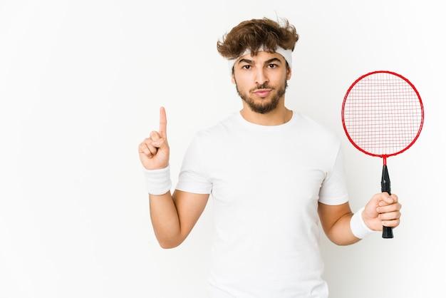 Junger indischer mann, der badminton spielt, das nummer eins mit finger zeigt.
