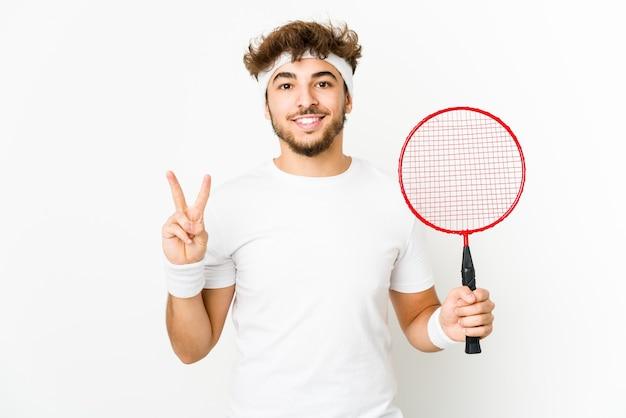 Junger indischer mann, der badminton spielt, das nummer zwei mit den fingern zeigt.