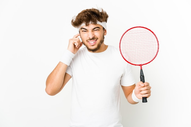 Junger indischer mann, der badminton spielt, das ohren mit händen bedeckt.