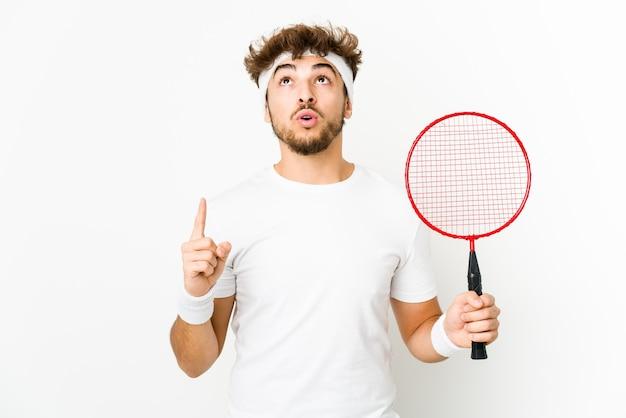 Junger indischer mann, der badminton spielt, der oben mit geöffnetem mund zeigt.
