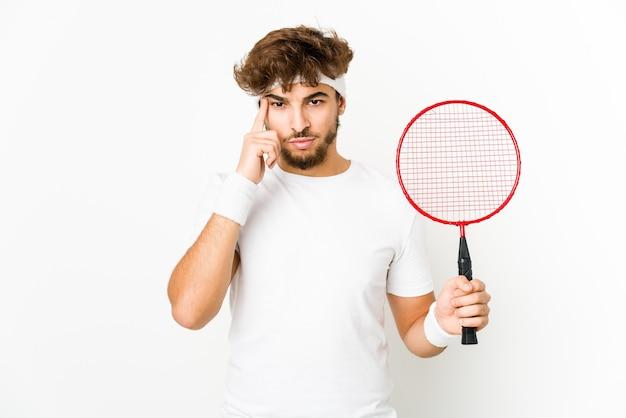 Junger indischer mann, der badminton spielt, der tempel mit dem finger zeigt, denkt, sich auf eine aufgabe konzentriert.