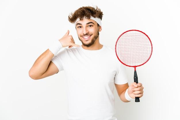 Junger indischer mann, der badminton spielt, zeigt eine handy-anrufgeste mit den fingern.
