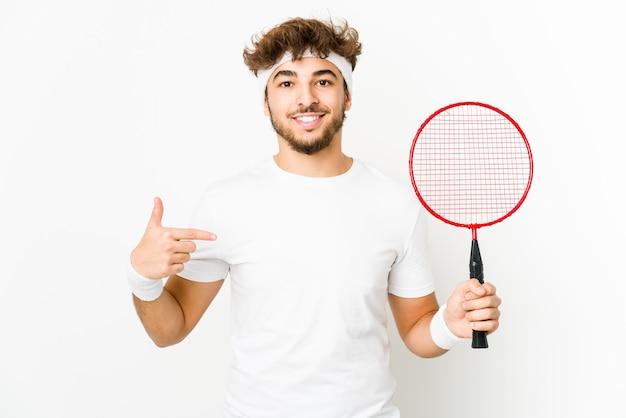 Junger indischer mann, der badmintonperson spielt, die von hand auf einen hemdkopierraum zeigt, stolz und zuversichtlich