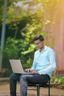 Junger indischer mann, der den laptop, arbeitend an laptop verwendet