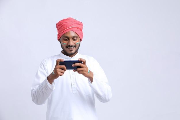 Junger indischer mann, der den tag der unabhängigkeit oder den tag der republik feiert und smartphone verwendet.