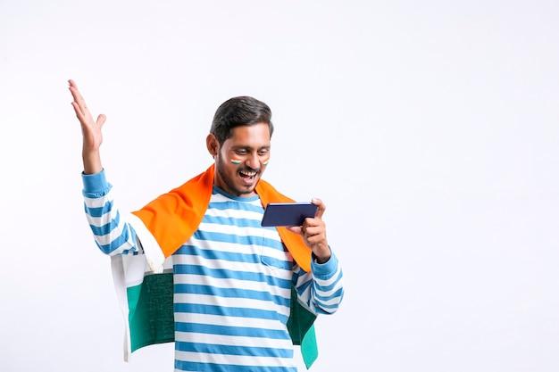 Junger indischer mann, der den tag der unabhängigkeit oder den tag der republik feiert und smartphone verwendet