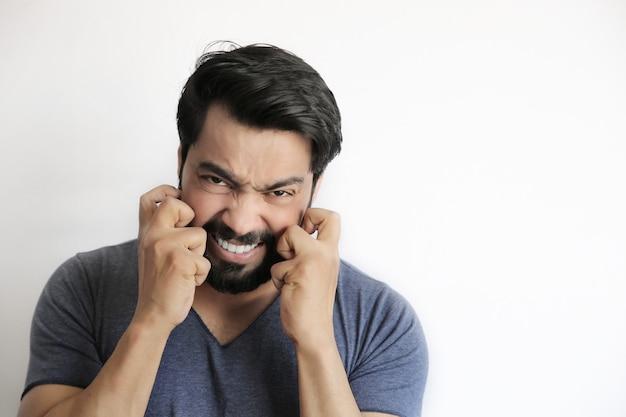 Junger indischer mann, der die finger kreuzt, glücksgeste - isolierter weißer hintergrund