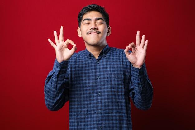 Junger indischer mann, der ein lässiges hemd trägt, das über isoliertem rotem hintergrund steht, entspannen und lächeln mit geschlossenen augen und tun meditationsgeste mit fingern yoga-konzept.