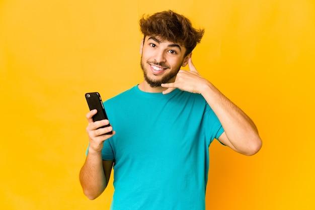 Junger indischer mann, der ein telefon hält, das eine handy-anrufgeste mit den fingern zeigt.