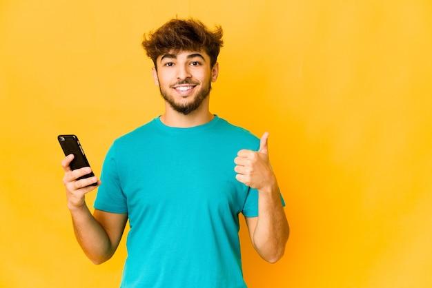Junger indischer mann, der ein telefon hält, das lächelt und daumen aufhebt