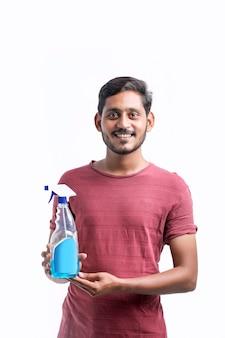 Junger indischer mann, der händedesinfektionsmittel zum schutz vor corona-virus verwendet.