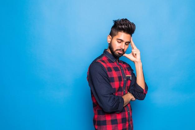 Junger indischer mann, der hemd mit hand auf kinn trägt, das über frage nachdenkt, nachdenklicher ausdruck, der über isoliertem blauem raum steht. mit nachdenklichem gesicht lächeln. zweifel konzept.