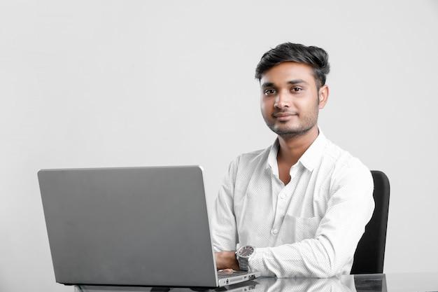 Junger indischer mann, der im büro arbeitet