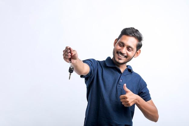 Junger indischer mann, der in der hand den schlüssel über weißem hintergrund hält.