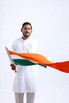 Junger indischer mann, der indische nationalflagge schwenkt. unabhängigkeitstag feiern
