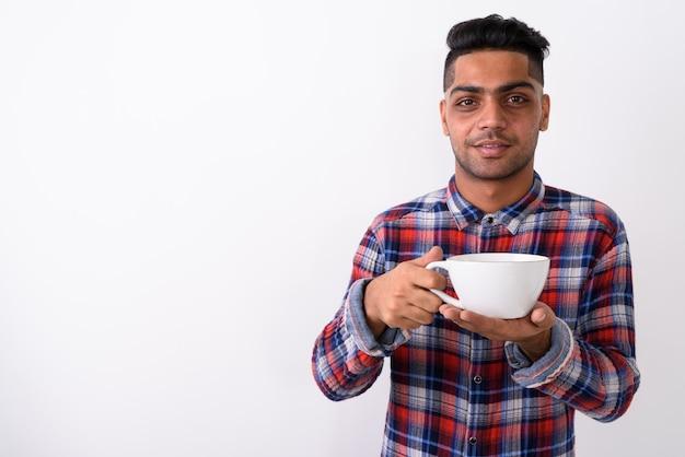 Junger indischer mann, der kariertes hemd auf weiß trägt