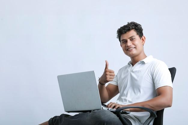 Junger indischer mann, der laptop verwendet.