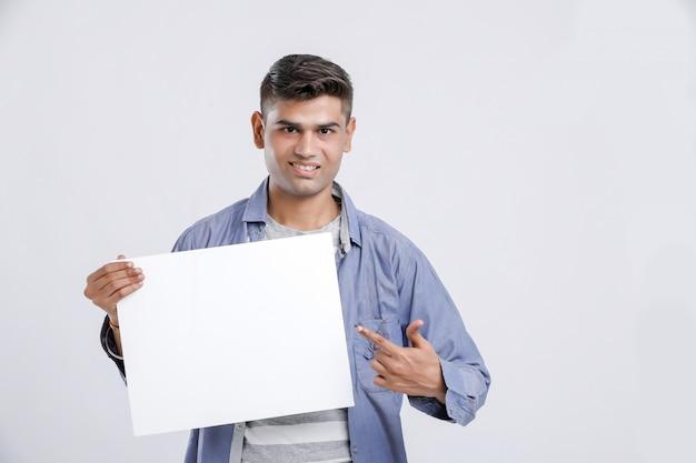 Junger indischer mann, der leeres zeichenbrett zeigt