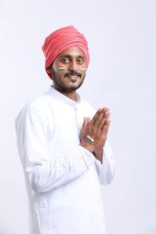 Junger indischer mann, der namaste oder willkommene geste gibt.