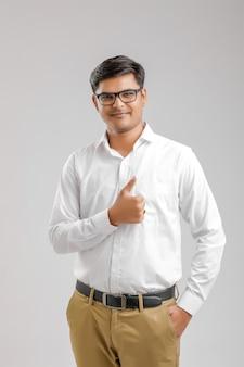 Junger indischer mann, der oben daumen steht und tut