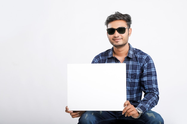 Junger indischer mann, der plakat hält