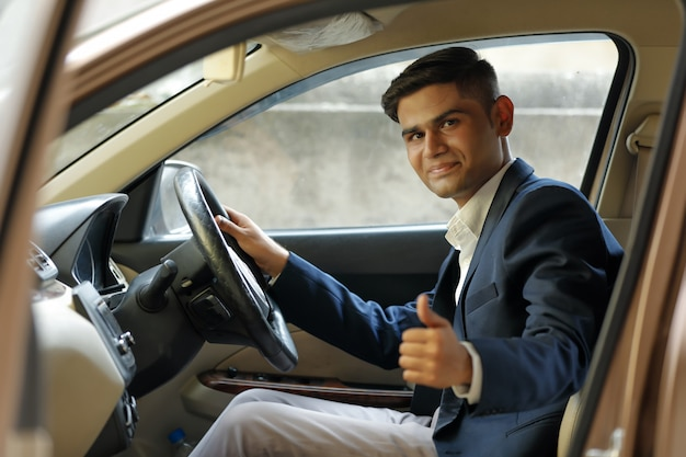 Junger indischer mann, der schläge oben vom autofenster zeigt