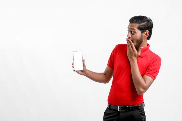 Junger indischer mann, der schockierenden ausdruck nach dem sehen im smartphone