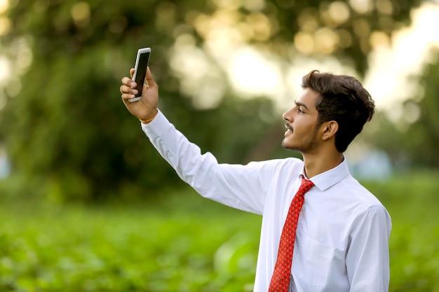 Junger indischer mann, der selfie mit handy klickt