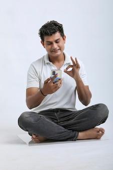 Junger indischer mann, der smartphone auf weißem hintergrund verwendet.