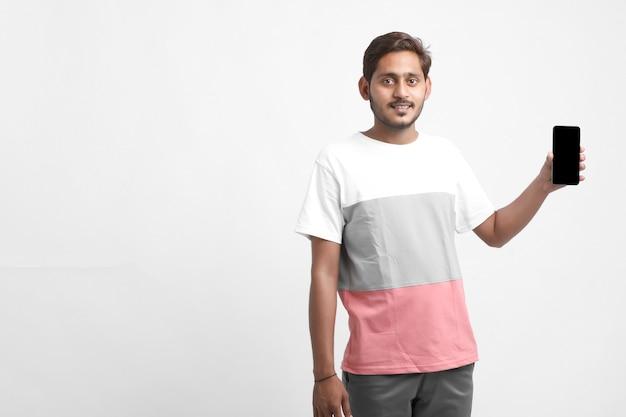Junger indischer mann, der smartphonebildschirm zeigt