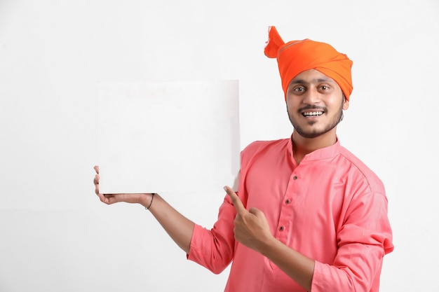 Junger indischer mann, der weißen karton auf weißer wand hält