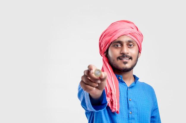 Junger indischer mann, der zehn rupien-münze auf weißem hintergrund zeigt.