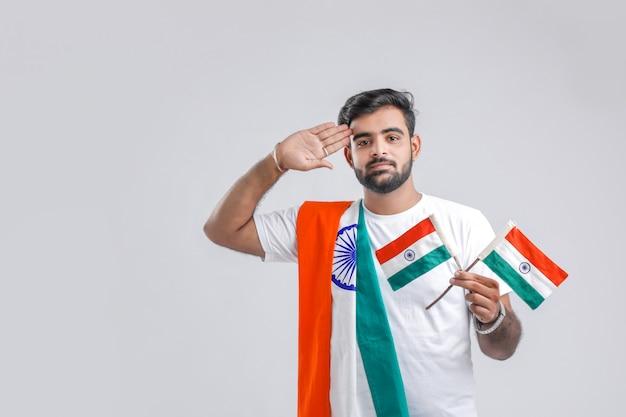 Junger indischer mann, der zur indischen flagge begrüßt