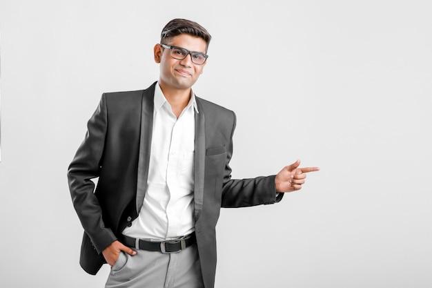 Junger indischer mann im anzug und in der richtung zeigend