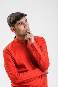 Junger indischer mann im roten hemd und in denkender großer idee auf weiß