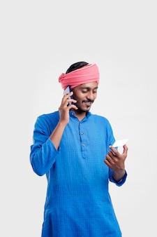 Junger indischer mann in traditioneller kleidung und auf smartphone sprechen und karte auf weißem hintergrund verwenden.