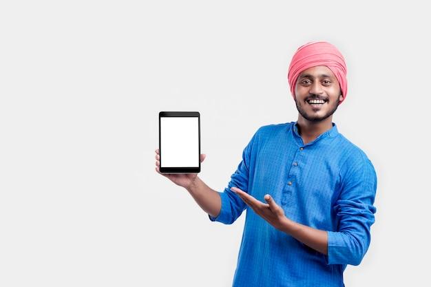 Junger indischer mann in traditioneller kleidung und mit tablet auf weißem hintergrund.