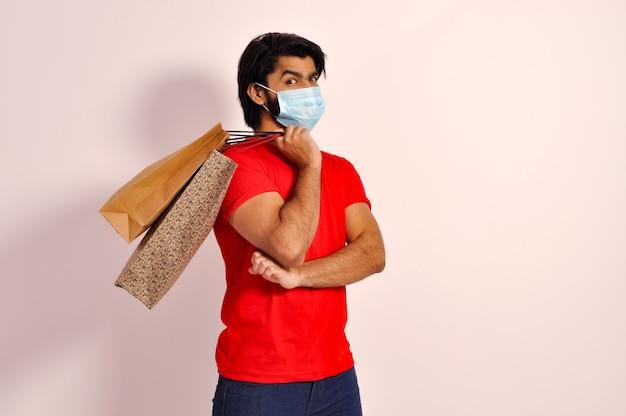 Junger indischer mann mit einkaufstüten, die eine maske tragen und beim einkaufen lächeln?