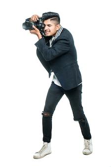 Junger indischer mann mit kamera lokalisiert über weißem hintergrund