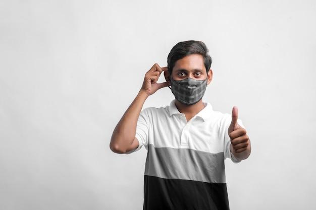Junger indischer mann mit maske zum schutz vor viren.